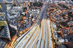 Aerial view of train tracks entering London Bridge illuminated at dusk