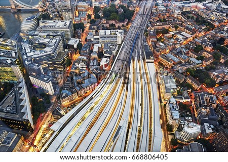 Aerial view of train tracks entering London Bridge illuminated at dusk  #668806405