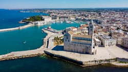 Aerial view of Trani in the southeastern region of Apulia in Italy - Entrance to the old port of Trani from above with the Cathedral of San Nicola Pellegrino on the coast of the Adriatic Sea