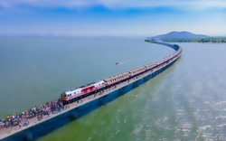 Aerial view of Travel train parked on a floating railway bridge above the reservoir of Pa Sak Jolasid dam for tourists to take a pictures at Lopburi, amazing Thailand.