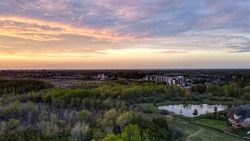 Aerial view of trees, a city skyline, and a pond during a beautiful red/pink sunset