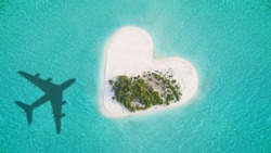 Aerial view of tropical island in heart shape with airplane shadow. Tropical paradise and beach holiday conceptual image.