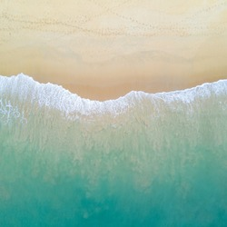 Aerial view of turquoise ocean wave reaching the coastline. Beautiful tropical beach from top view. Andaman sea in Thailand. Summer holiday vacation concept
