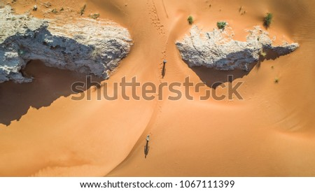 Aerial view of two persons walking in the desert of Sharjah, U.A.E.