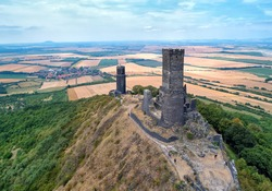 Aerial view of two stone towers,  ruins of medieval castle Hazmburk, Hasenburg built on top of the mountain peak, surrounded by agriculture czech landscape. Attraction, castles of western Bohemia.