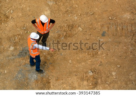 Aerial view of two unrecognised civil engineers inspecting construction site. Building development concept with copy space