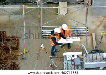 Aerial view of two unrecognized civil engineers inspecting construction site. Building development concept.
