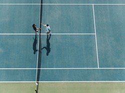 Aerial view of two young man shaking hands on hard court. Tennis players shaking hands over the net after the match.