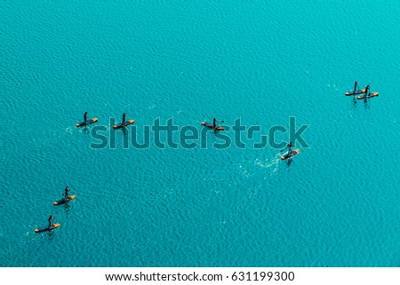 Aerial view of unrecognizable group of people stand up paddle boarding on water surface for sport, fun, leisure or recreational pursuit. Enjoying summer SUP activity for holiday vacation. #631199300