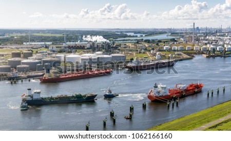 Aerial view of various oil tankers at a busy oil storage terminal port.