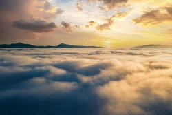 Aerial view of vibrant sunset over white dense clouds with distant dark mountains on horizon.