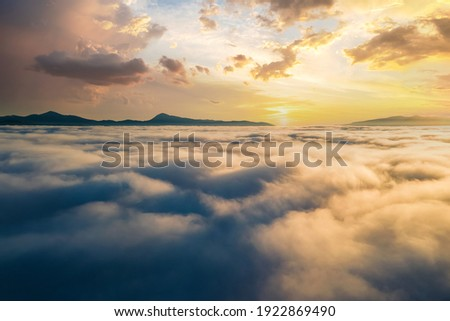 Aerial view of vibrant sunset over white dense clouds with distant dark mountains on horizon. Сток-фото ©