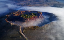aerial view of volcanic crater in Racos village, Brasov county, Romania - foggy autumn morning