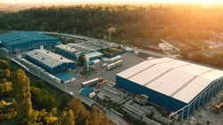 Aerial view of warehouse storages or industrial factory or logistics center from above. Aerial view of industrial buildings and equipment machines at sunset, toned