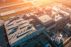 Aerial view of warehouse storages or industrial factory or logistics center from above. Aerial view of industrial buildings and equipment at sunset, toned