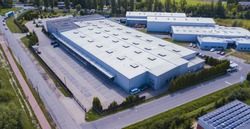 Aerial view of warehouse storages or industrial factory or logistics center from above. Top view of industrial buildings and trucks
