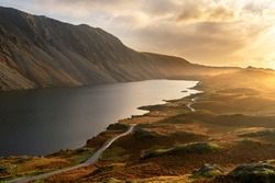 Aerial view of Wastwater lake in the English Lake District with rural road leading through the landscape.