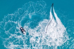 Aerial view of water extreme action sport, summer sea, close to luxury tropical resort . Fly board in ocean lagoon, freedom fun as summer recreational activity. Flyboard view from drone