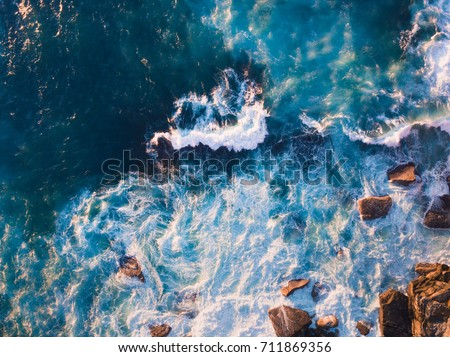 Aerial view of waves and some of rocks. #711869356