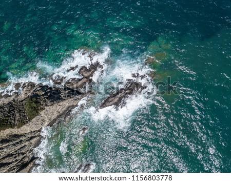 Aerial view of waves crashing into coastal rocks. #1156803778