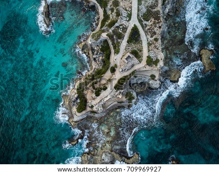 Shutterstock Aerial view of waves crashing on Punta Sur - Isla Mujeres, Mexico - with brilliant blue water, crashing waves and rocky shoreline.