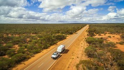 Aerial View of 4WD vehicle and modern caravan travelling a highway in the outback of Australia