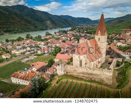 Aerial view of Weissenkirchen beautiful village with wineries in the Wachau region along the Danube in Austria with medieval fortified Roman Catholic church