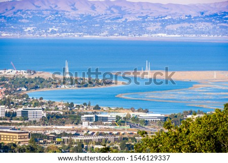 Aerial view of wetlands in the San Francisco Bay Area; Office buildings, residential areas and electricity towers visible on the shoreline; San Carlos, California