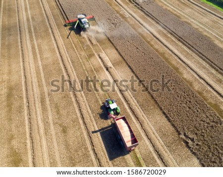 Aerial view of wheat field being harvested by combine harvester with trailer and grain in foreground