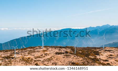 Aerial view of wind farm in rural area on bright sunny day in