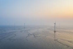 aerial view of wind farm on tidal flat wetland in sunrise, clean energy landscape