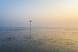 aerial view of wind farm on tidal flat wetland in sunrise, sustainable energy landscape, jiangsu province, China.