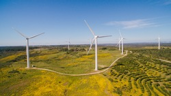 Aerial view of Wind Generating stations in green fields on a background of blue sky. Portugal.