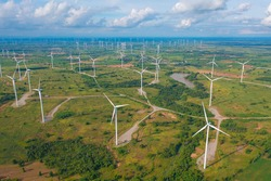 Aerial view of wind turbines or windmills farm field in industry factory. Power, sustainable green clean energy, and environment concept. Nature innovation.