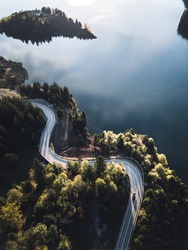 Aerial view of winding road with blue lake. Great road trip trough the dense woods. Aerial view with green foliage in Colibita, Romania