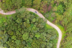 Aerial view of winding road with pine tree forest in mountain.Scenery Bird eye view of asphalt road landscape.High view from drone save drive transport and journey in countryside concept