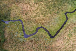 Aerial view of windling river in zig zag formation in desolate landscape environment