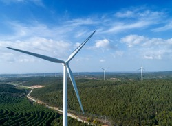 Aerial view of windmills or wind turbine on wind farm in rotation to generate electricity energy