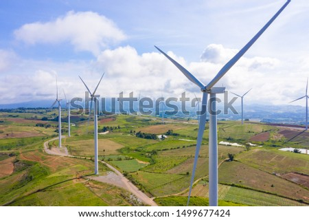 Aerial view of windmills rotating by the force of the wind for generating clean renewable energy for sustainable development in a green ecologic way on beautiful cloudy sky at highland. #1499677424