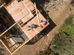 Aerial view of woodworkers on the roof of a tiny house
