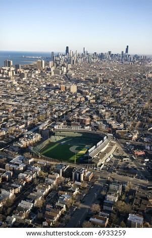 Aerial view of Wrigley Field with Chicago, Illinois skyline in background.