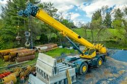 Aerial view of yellow heavy duty jib equipped  telescopic crane at a road widening construction site with boom nose surrounded by rusty steel pipes and concrete road blocks