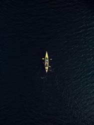 aerial view of yellow kayak in dark blue lake water. Drone photo