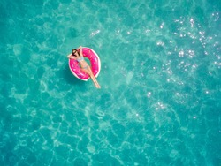 Aerial view of young brunette woman swimming on the inflatable big donut in the transparent turquoise sea. Top view of slim lady relaxing on her holidays in Thailand, Phuket, Andaman sea.