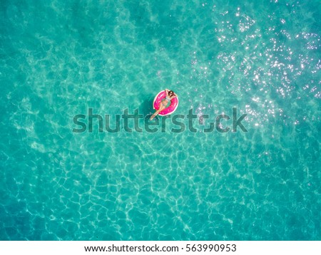 Stock Photo Aerial view of young brunette woman swimming on the inflatable big donut in the transparent turquoise sea. Top view of slim lady relaxing on her holidays in Thailand, Phuket, Andaman sea.