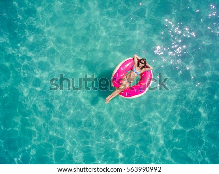 Aerial view of young brunette woman swimming on the inflatable big donut in the transparent turquoise sea. Top view of slim lady relaxing on her holidays in Thailand, Phuket, Andaman sea. #563990992