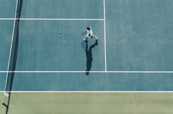 Aerial view of young male tennis player walking on hard court to pick the ball. Professional tennis player on club court.
