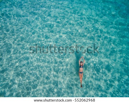 Aerial view of young woman in bright bikini is swimming in the transparent, blue sea. Top view of slim woman floating on the water of Andaman sea. Khai Nok island, Phuket, Thailand. #552062968