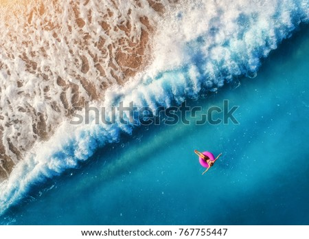 Aerial view of young woman swimming on the pink swim ring in the transparent blue sea in Oludeniz,Turkey. Summer seascape with girl, beautiful waves, azure water at sunset. Top view from drone. Travel #767755447