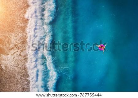 Aerial view of young woman swimming on the pink swim ring in the transparent turquoise sea in Oludeniz. Summer seascape with girl, beach, beautiful waves, blue water at sunset. Top view from drone #767755444